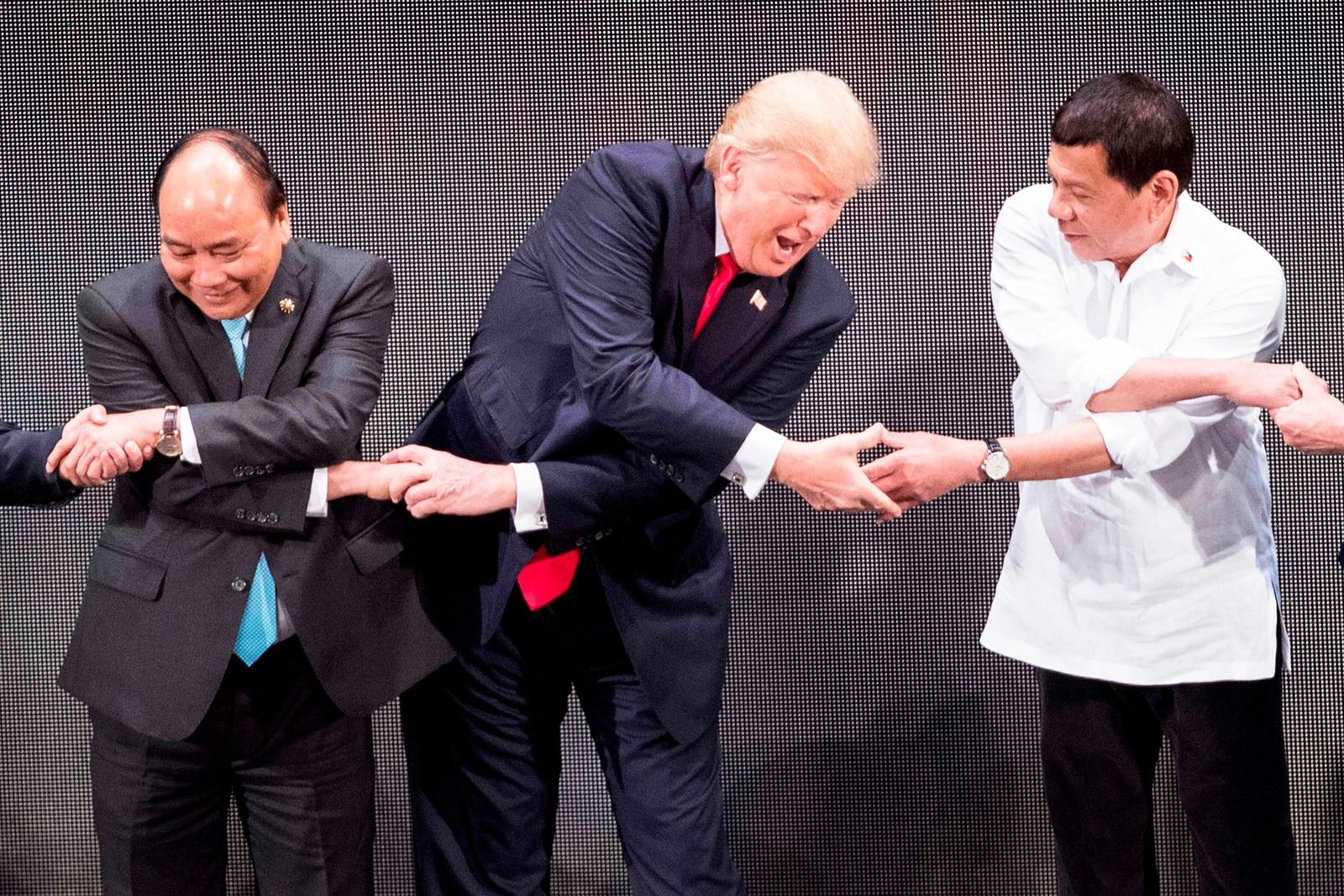 Etter at han skjønte hvordan det virket tok president Donald Trump både Vietnams statsminister Nguyen Xuan Phuc (t.v.) og Filippinenes president Rodrigo Duterte (t.h) i hendene.