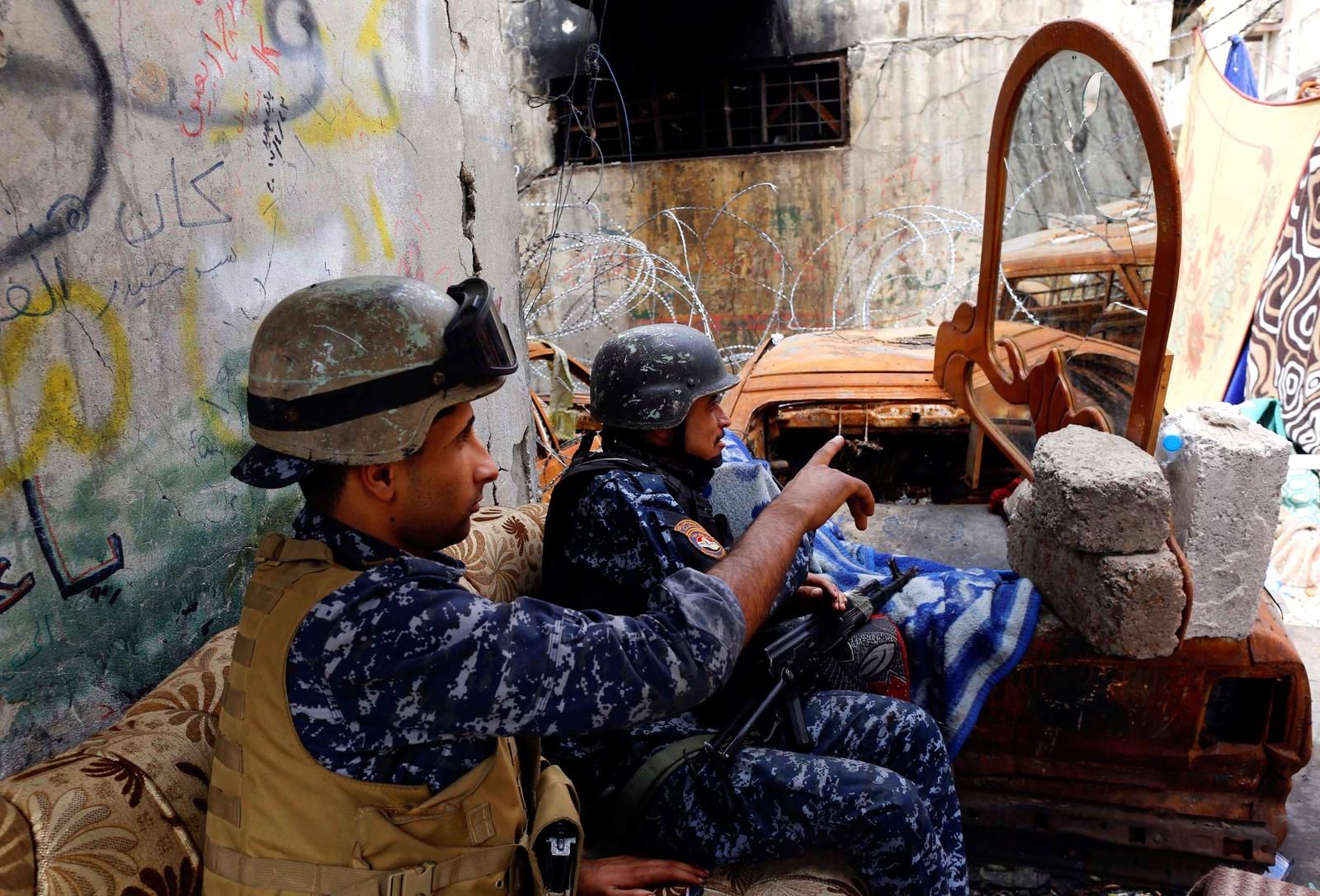 Irakiske politimenn forsøker å få øye på IS-krigere i Mosul.
