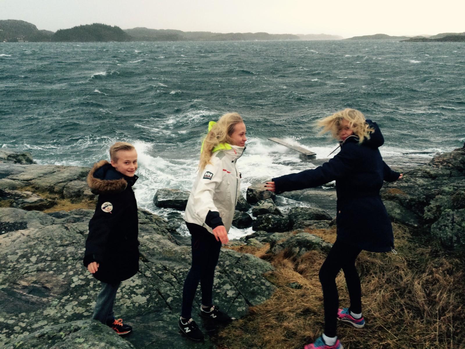 """LEK I VINDEN: Uværet røsket godt på Glesvær, syd på Sotra. Men disse tre lot seg ikke affisere av """"Tor""""."""