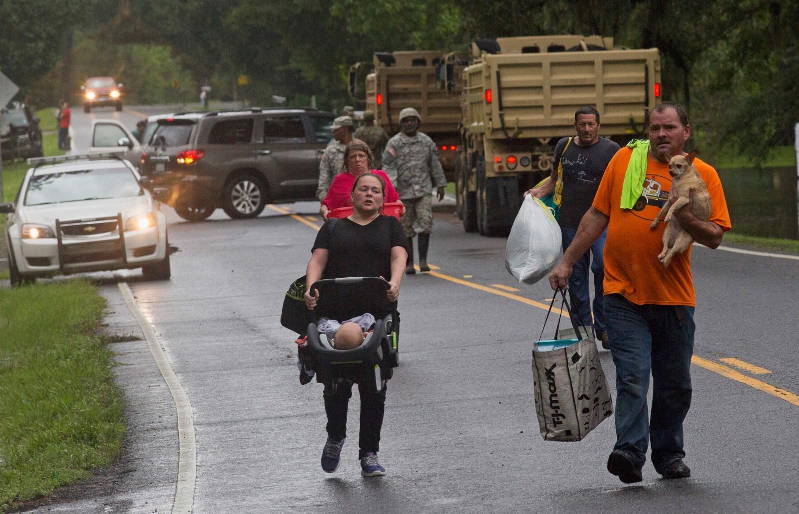 RØMMER: Nasjonalgarden i Louisiana hjelper folk med å evakuere fra de flomrammede områdene.