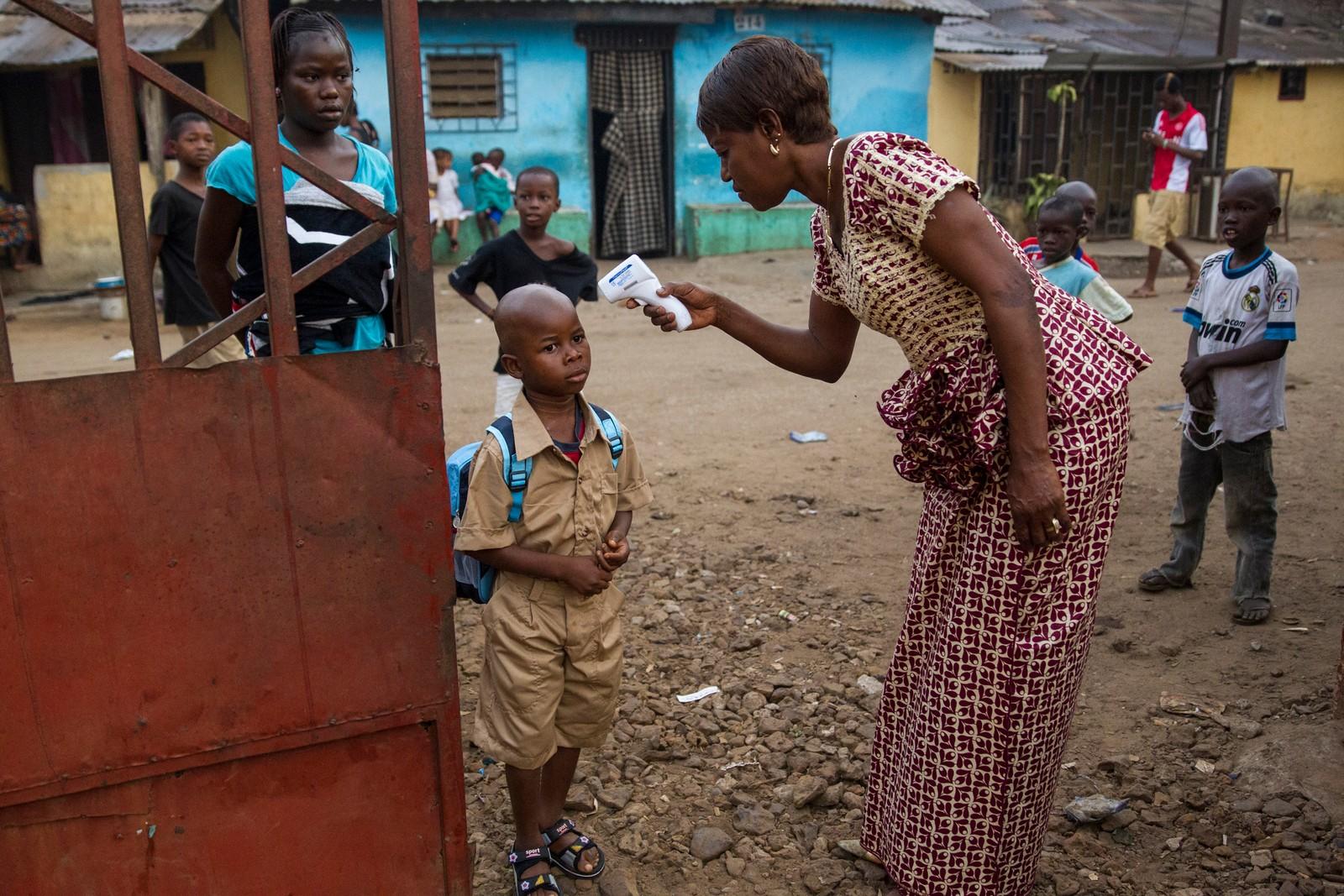 En kvinne måler temperaturen på et barn som ankommer Coleyah Centre Primary School, i Conakry i Guinea, for å passe på at barna ikke smitter hverandre med blant annet Ebola. Fotografert januar 2015.