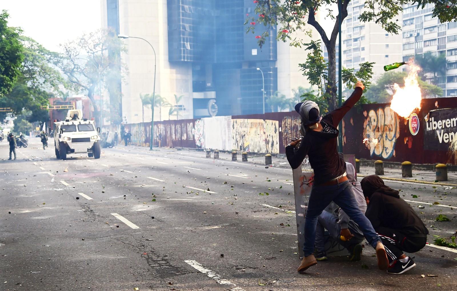 En demonstrant kaster en såkalt Molotov-cocktail mot opprørspolitiet.