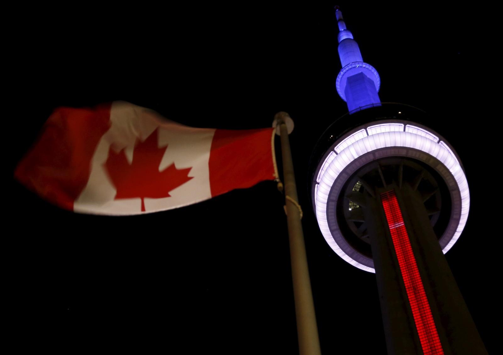 Landemerket «CN Tower» i Toronto, Canada, lyser i blått, hvitt og rødt bak det kanadiske flagget.