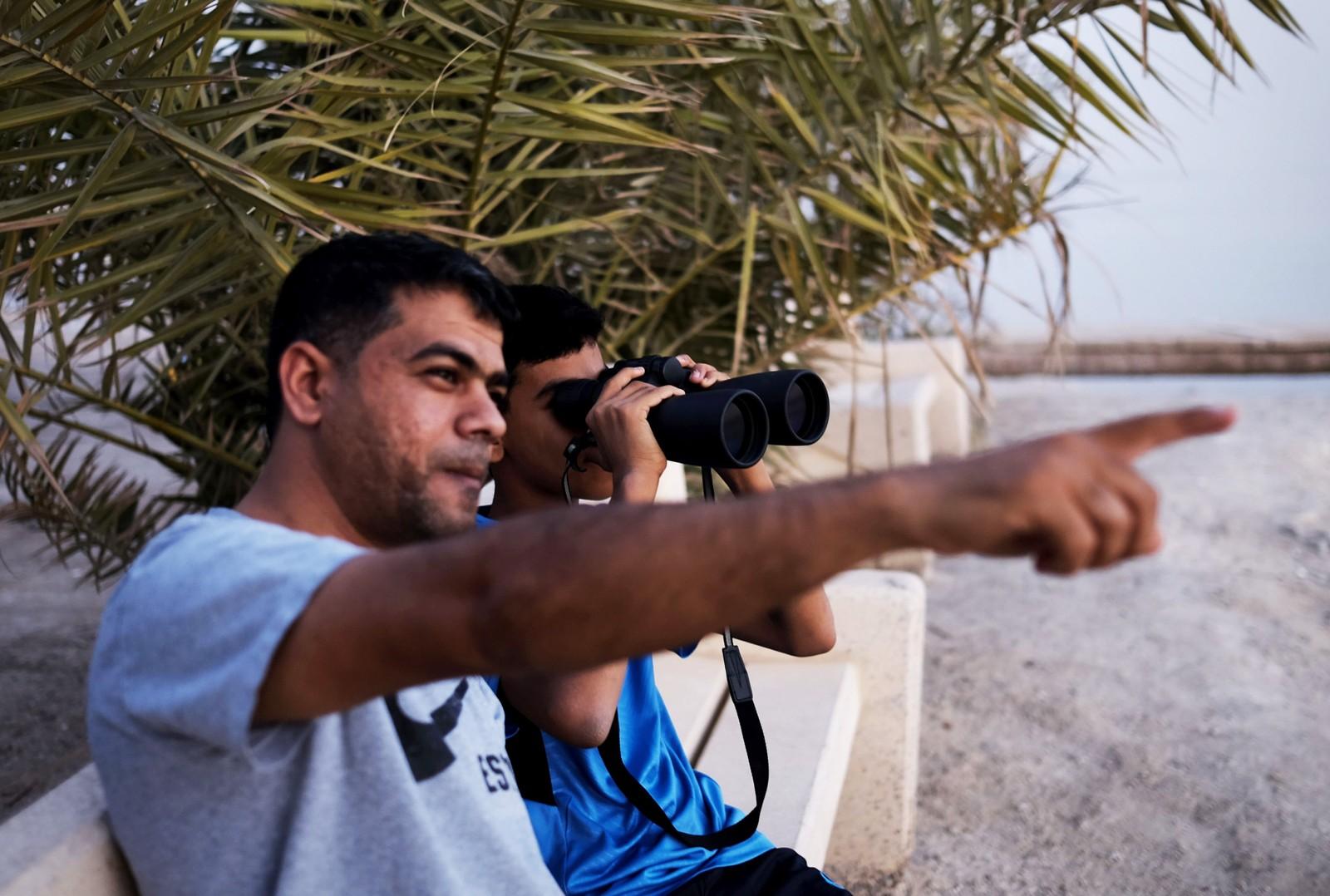To menn speider etter det første glimt av nymånen som innleder ramadan på stranden i Karzakkan, sør for Manamai i Bahrain.