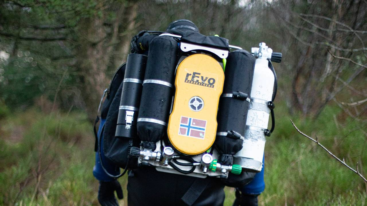 Espen Rekdal går gjennom skogen ikledd dykkerutstyr og med oksygenflasker på ryggen