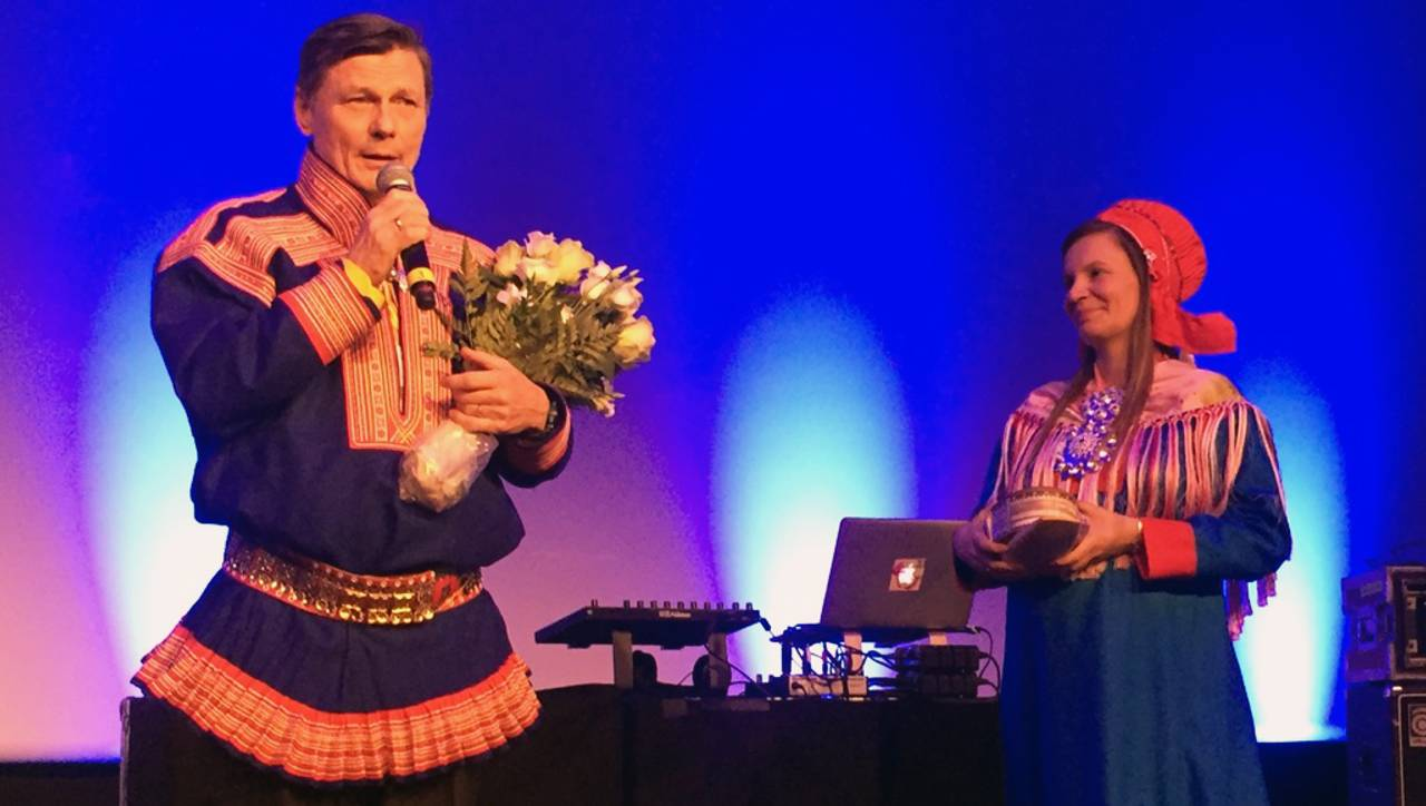 Ole Henrik Magga med mikrofon og blomster sammen med Áile Javo
