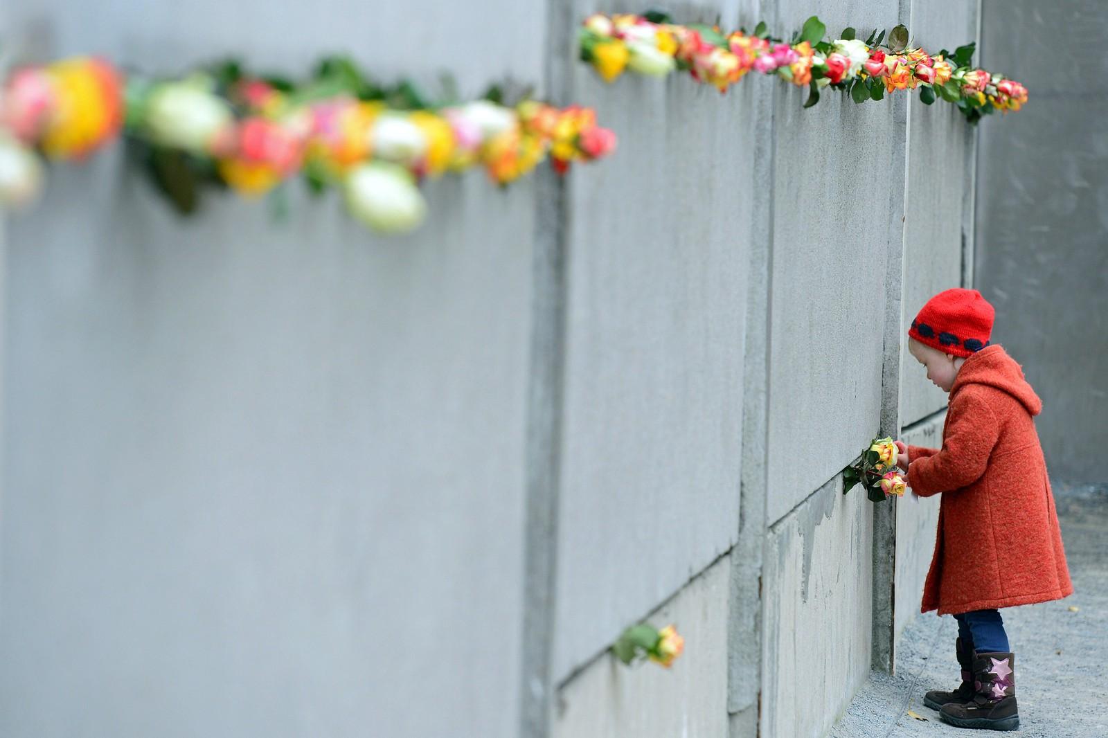 En jente ved en rest av muren.