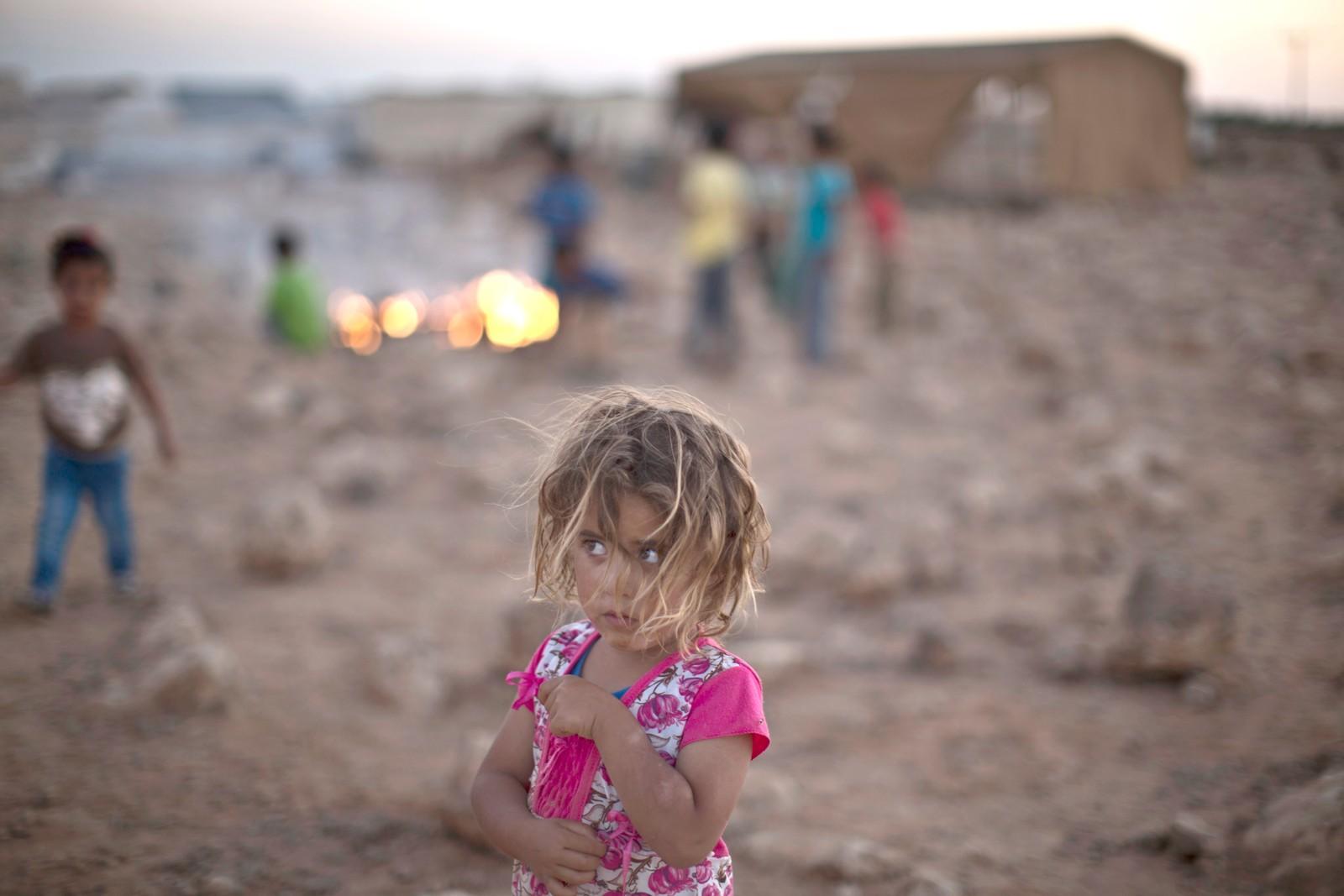 Syriske Shahd Qadura (2,5) har rømt fra sitt krigsherjede hjemland og bor nå i en midlertidig teltleir i utkanten av Mafraq i Jordan. Bak henne kan man se andre flyktningebarn som brenner søppel.