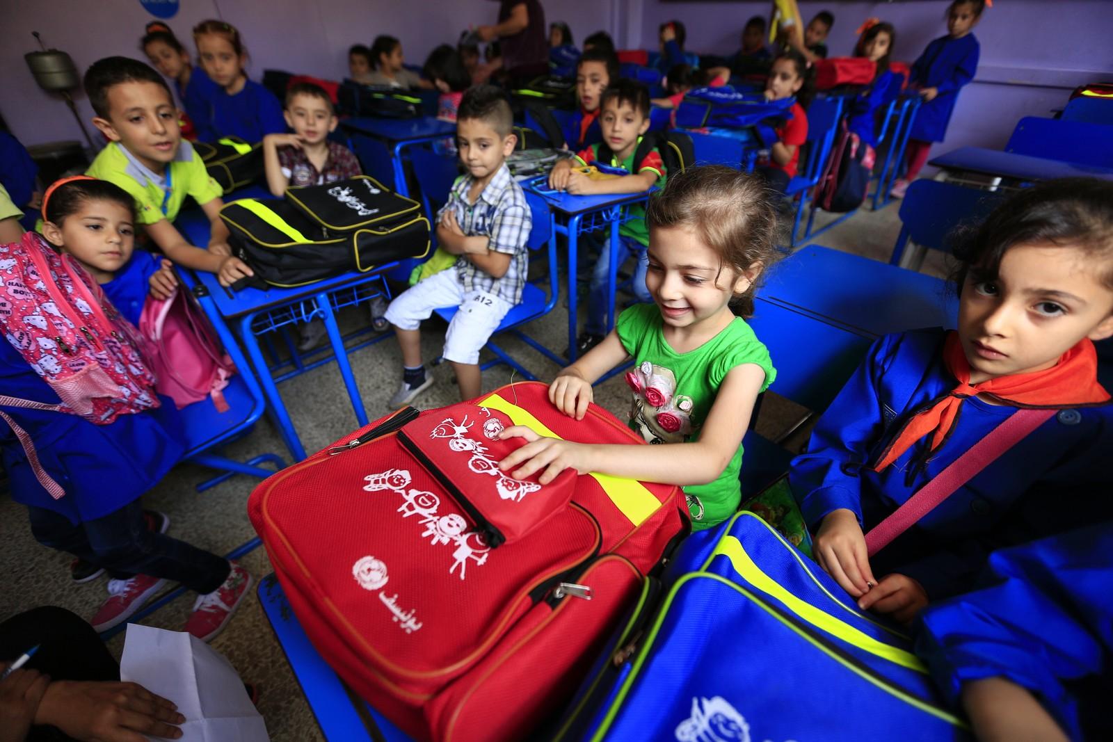 6 år gamle Fatima smiler etter å ha fått ny sekk på sin første skoledag. 100 barn startet opp på skolen Nazem Atrash Primary school i Homs høsten 2015.
