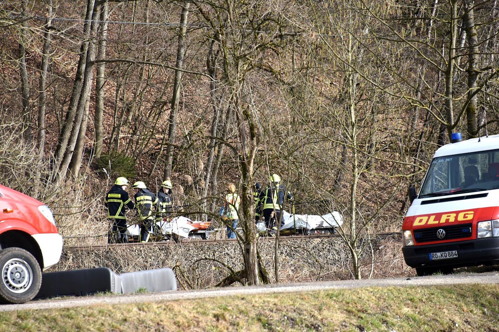 Brannmannskaper frakter bort døde etter togulykken.