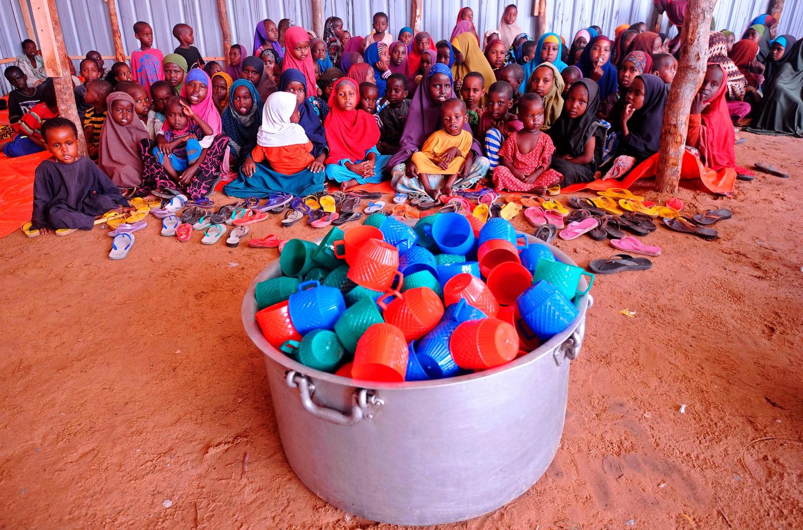 Somaliske flyktningbarn venter på mat utenfor Mogadishu i Somalia. Det er mange flyktninger som kommer til hovedstaden fra sør i landet, hvor de er hardt rammet av tørke.