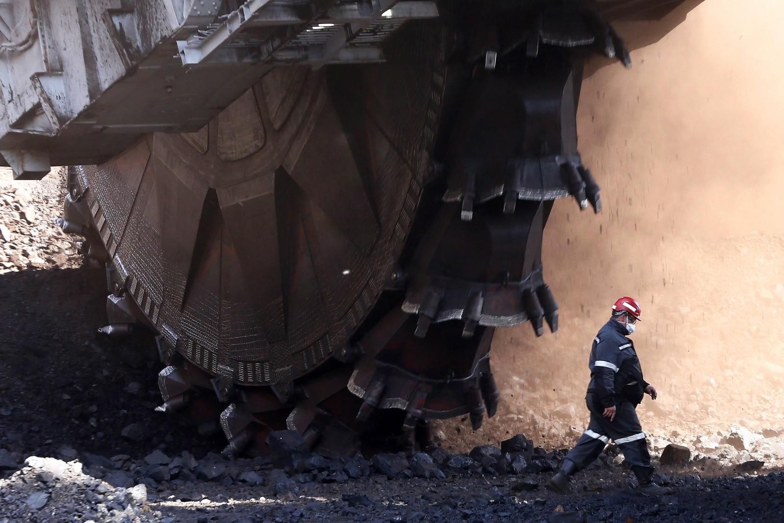 Truende tenner. En mann går forbi en anleggsmaskin fra sovjettiden som brukes til å utvinne kull ved den sibirske byen Sjarypovoi i Russland.