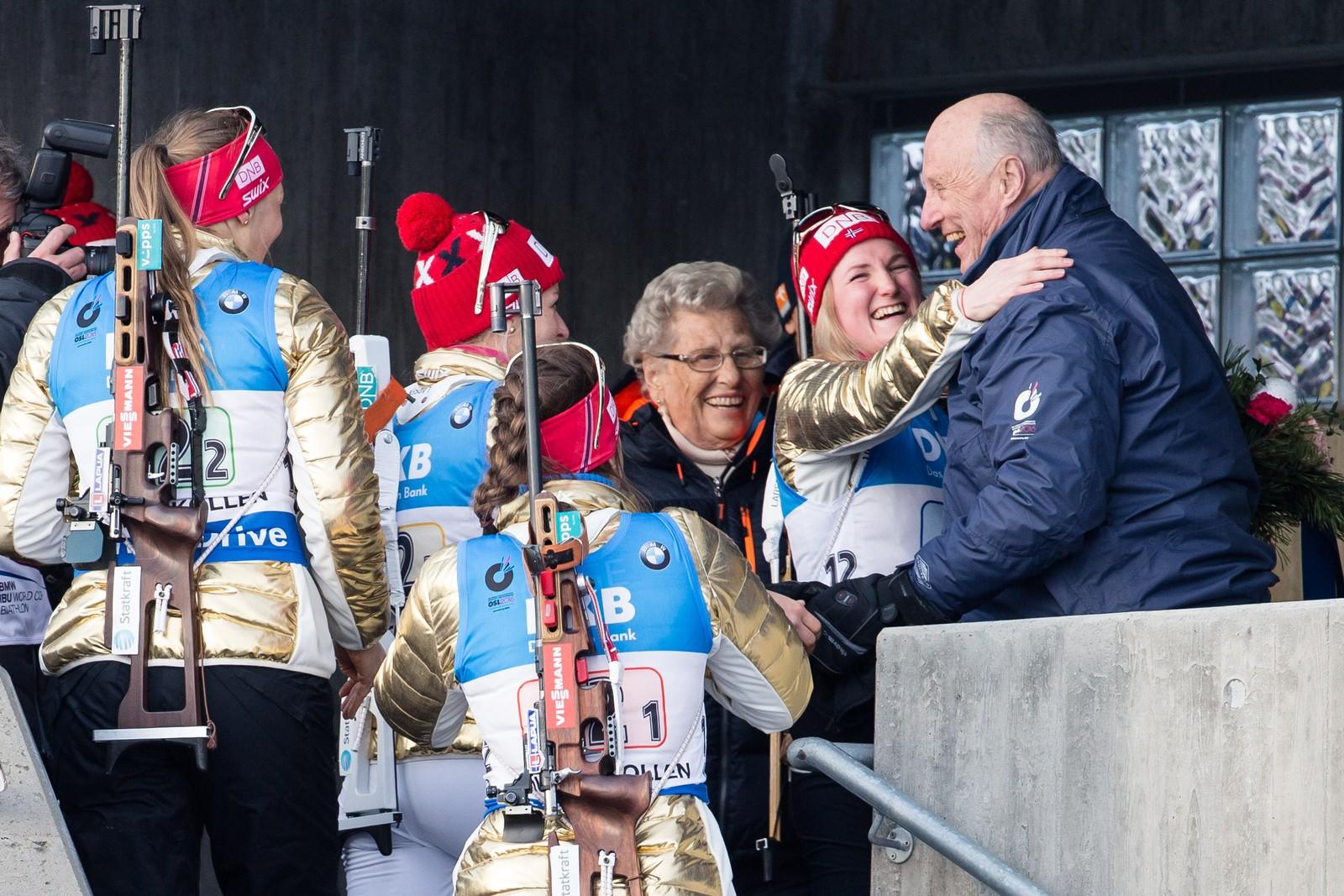 Marte Olsbu klemmer og hilser på kong Harald og prinsesse Astrid etter gullet på stafett kvinner i VM i skiskyting i Holmenkollen fredag.