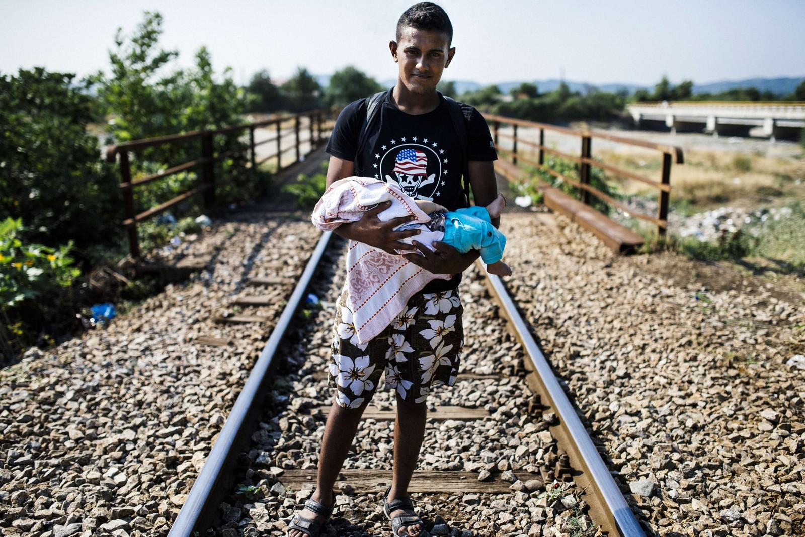 En migrant bærer barnet sitt langs jernbaneskinnene ved grensa mellom Hellas og Makedonia. Svært mange migranter forsøker å krysse grensa fra Serbia eller Makedonia og inn til EU i dette området.