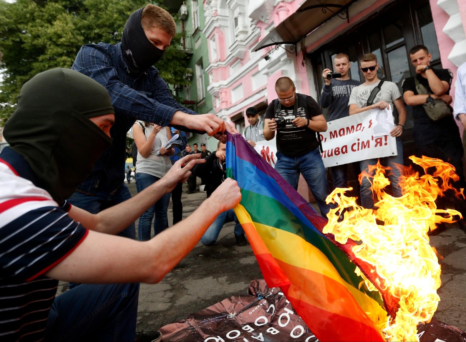 Demonstranter brant et regnbueflagg foran Amnesty-bygningen Kiev i forbindelse med Pride-uka i den ukrainske hovedstaden.
