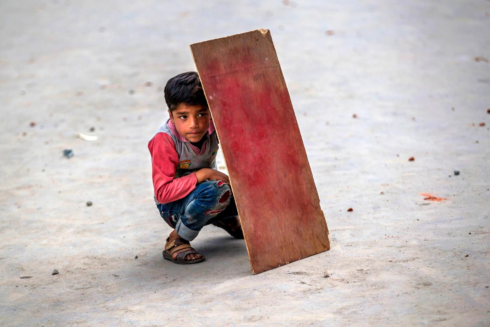 En gutt fra Kashmir forsøker å beskytte seg under et oppgjør mellom politiet og demonstranter i Srinagar i India. Demonstrantene krever at politiske fanger skal løslates fra indiske fengsler.