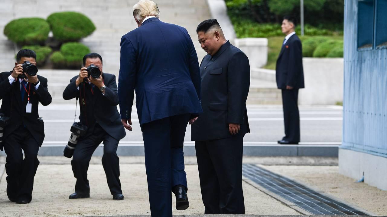 USAs president Donald Trump i det han skal sette foten ned på nordkoreansk jord med Kim Jong-un