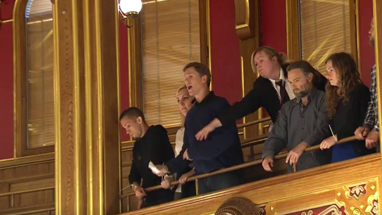 Dag Kolstø fra aktivistgruppa Extinction Rebellion roper ut sitt budskap fra galleriet på Stortinget.