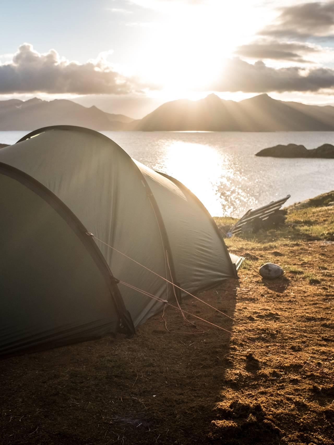 Telt i Lofoten sol i bakgrunn.