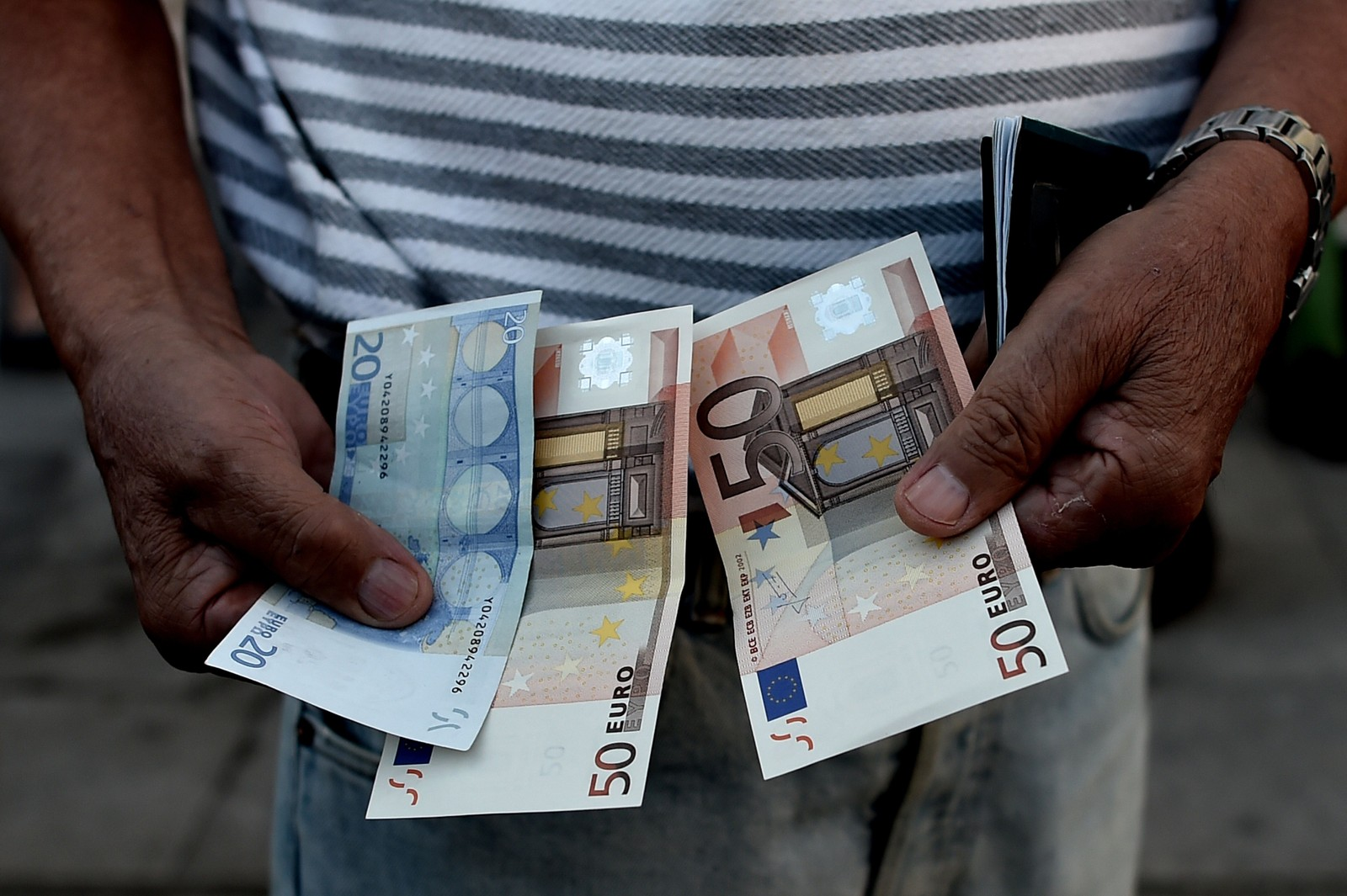 En gresk pensjonist holder fram pengene han fikk tatt ut. Hver enkelt får maksimalt tatt ut 120 euro.