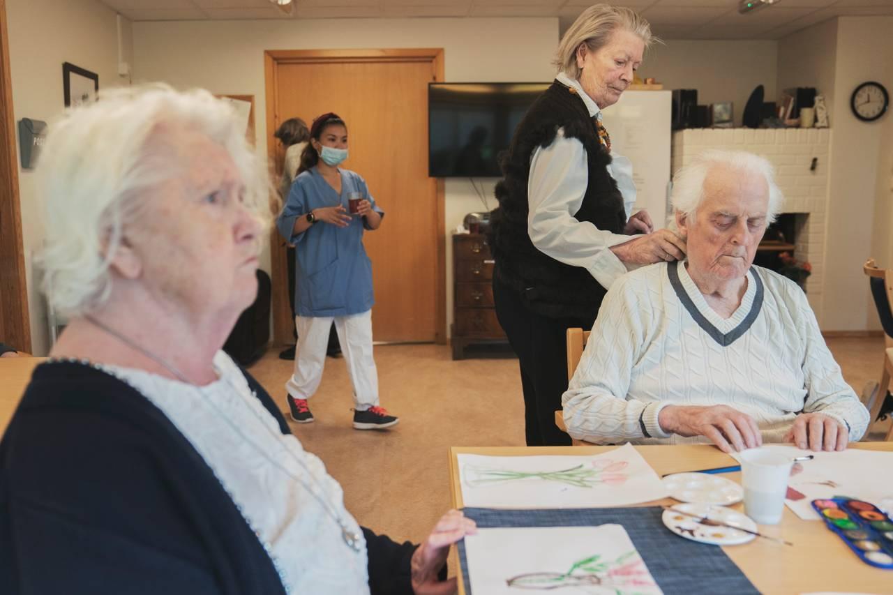 Anne Marie og ekteparet danser og maler ved et stort bord i et oppholdsrom.