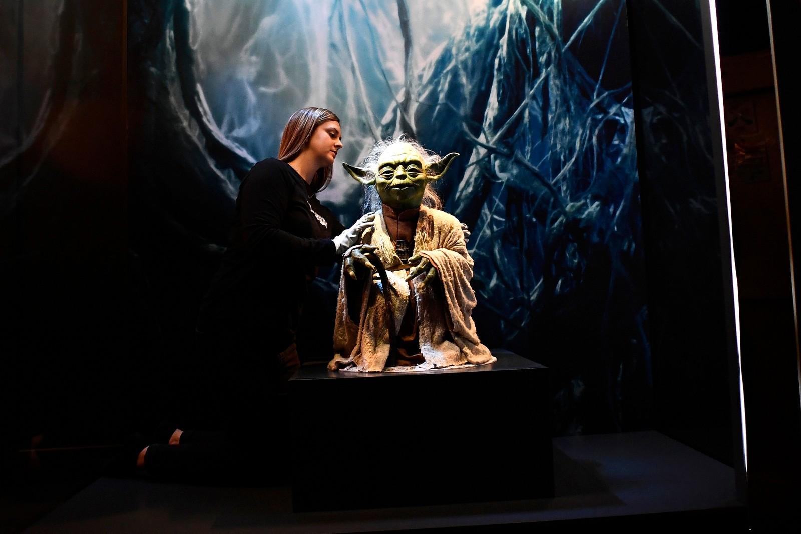 Kathy Smeaton, som jobber for ved Lucas Museum of Narrative Art, står sammen med Yoda-dukken som ble brukt i Star Wars-filmene. Man kan se Yoda og annet fra filmene på en utstilling i London.