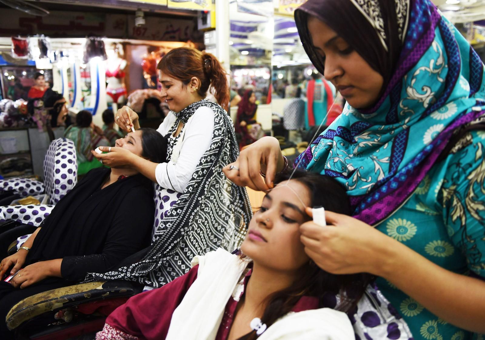 KARACHI: Pakistanske kvinner gjør seg klare for Eid på skjønnhetssalong i Karachi.