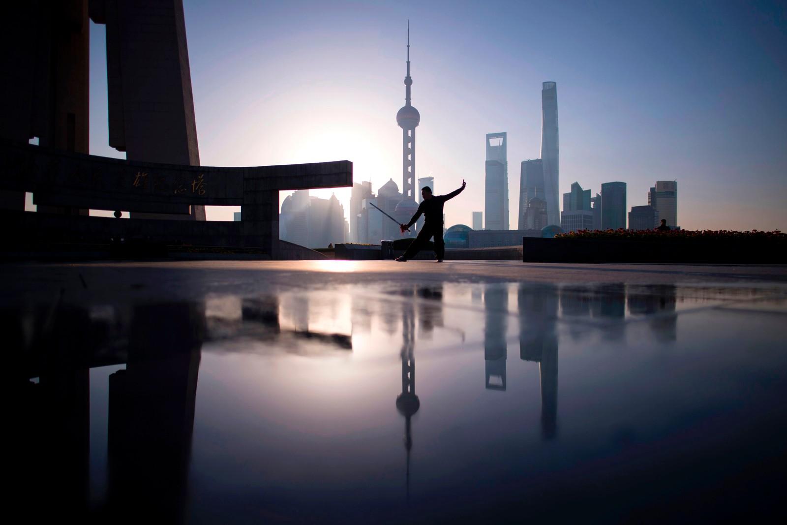 En mann viser fram Tai Chi-kunster tidlig en morgen i Shanghai.