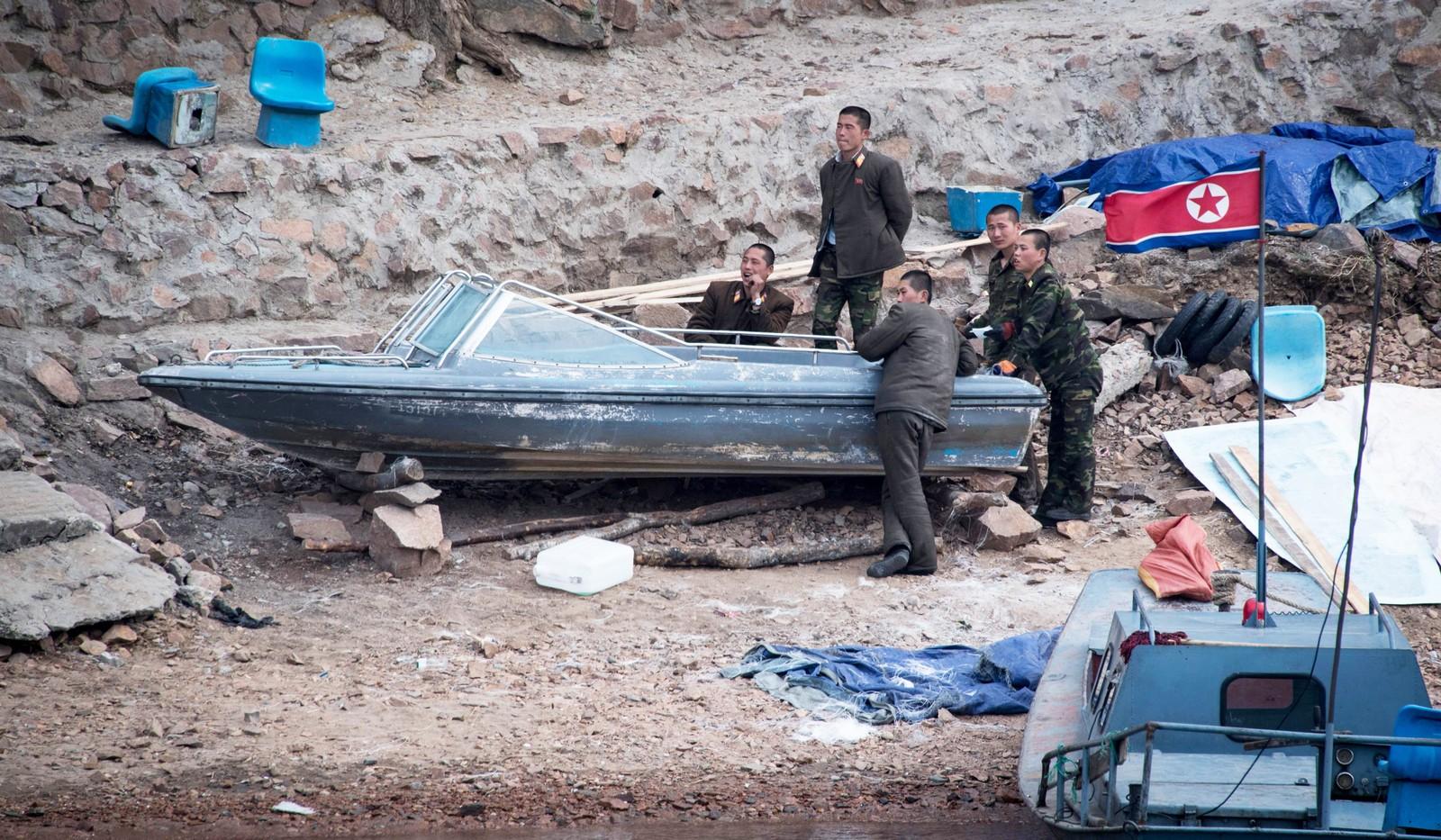 Nordkoreanske soldater med en båt ved Yalu-elva.