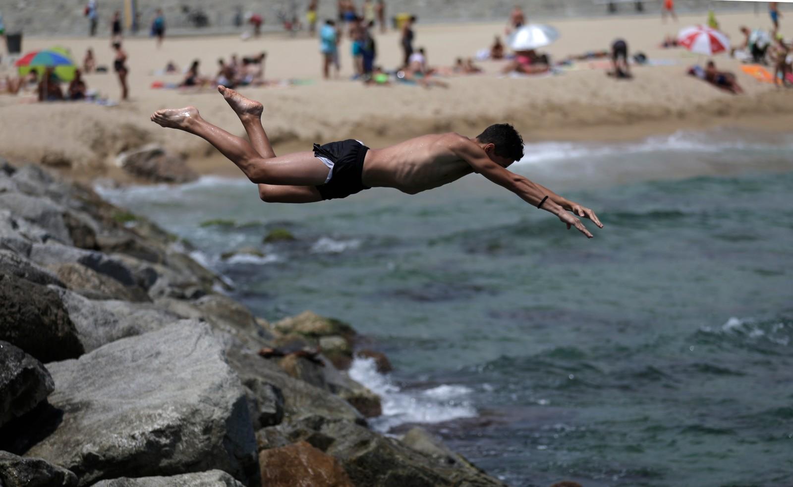 Ein gut hopper ut frå eit svaberg utanfor Barcelona i Spania. Temperaturane i landet har vore over 40 grader fleire gonger denne sommaren.