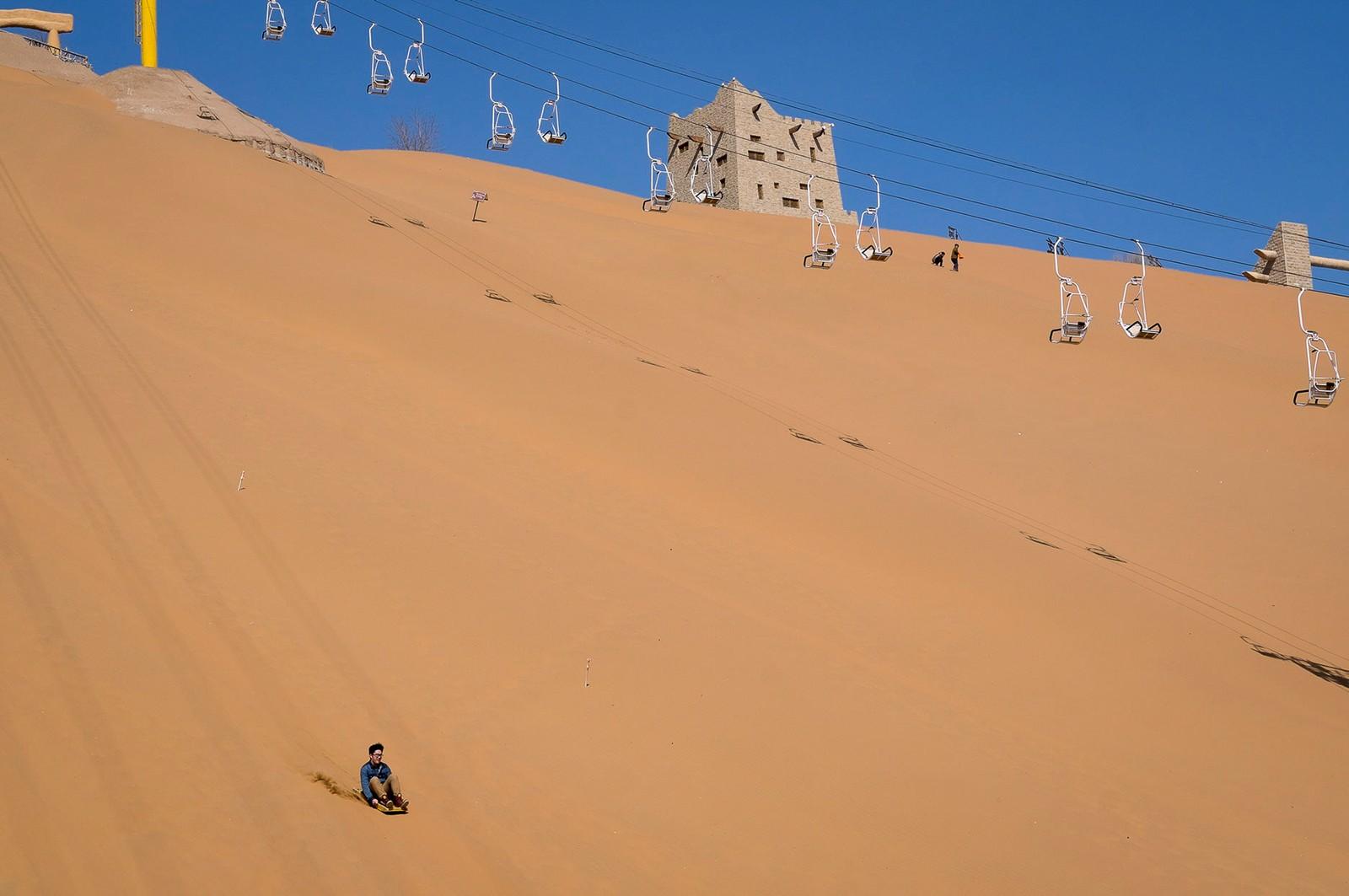 2. plass klima og miljø:  Forørkning er et av de største miljøproblemene i Kina. Rundt 20 prosent av Kinas landareal er ørken, og den spiser årlig store deler av dyrkbar jord. I byen Zhongwei i Ningxia provinsen har kinesiske myndigheter startet prosjektet The Great Green Wall of China for å hindre spredning. Samtidig har Shapotou Desert Resort blitt et populært reisemål for kinesere. Her kan de ake på sanddyner, kjøre Jeep gjennom ørkenen og ri på kameler. Juryens begrunnelse: En absurd konsekvens av klimaforandringer. Bildet har en god komposisjon, og det er noe umiddelbart over det.