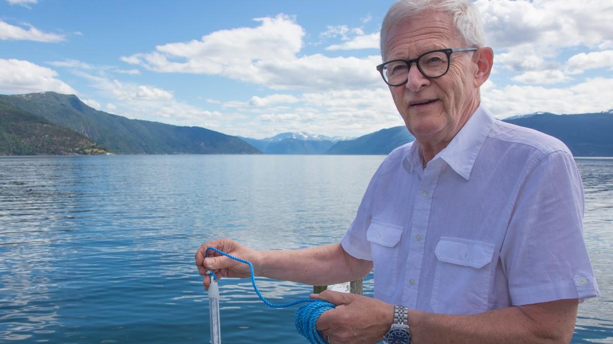 Jon Gjeraker måler badetemperaturen ved Midtnes hotel i Balestrand juni 2020.