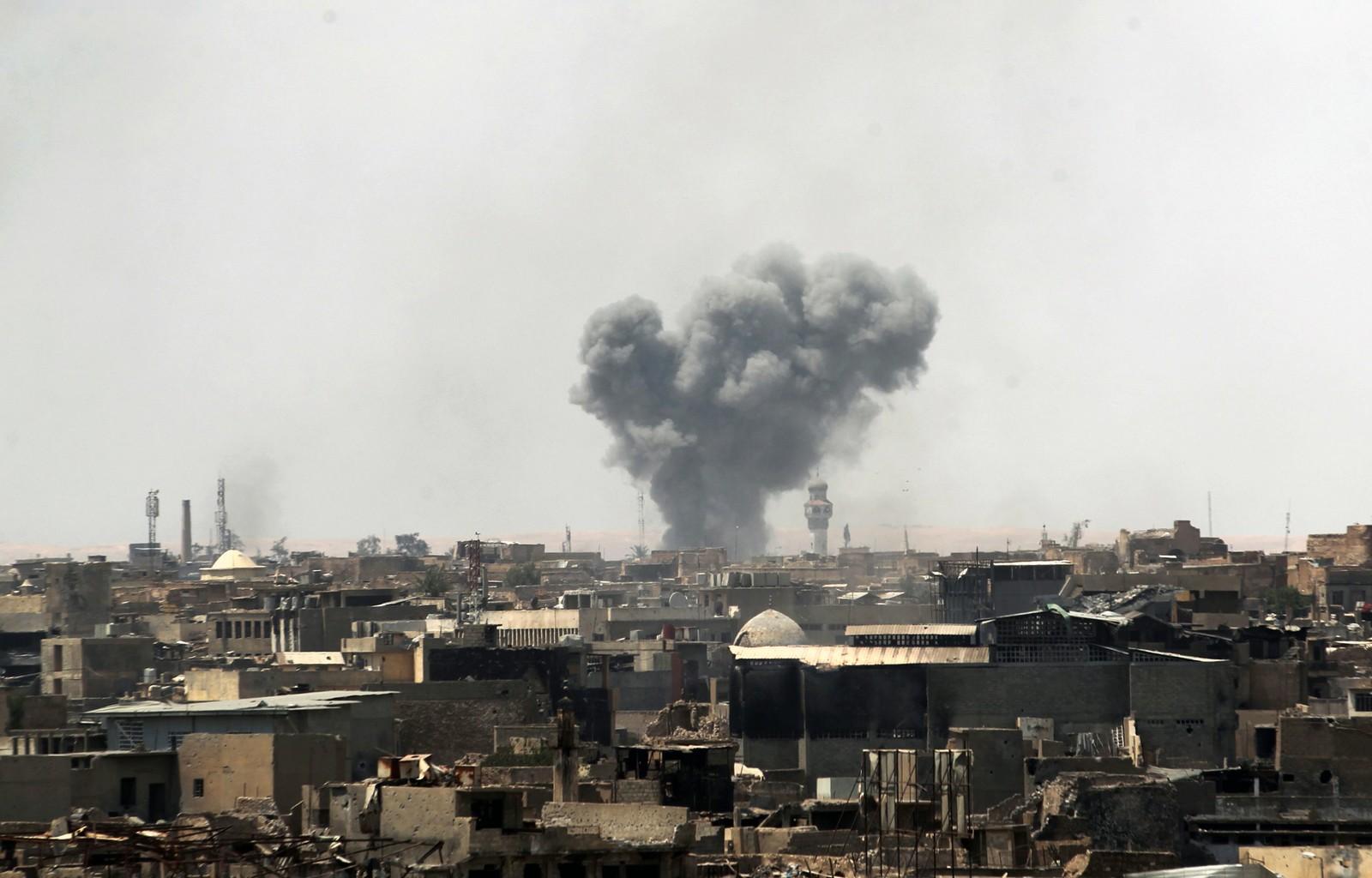 En røyksky over gamlebyen i Mosul søndag. Den amerikanskledede koalisjonen begynte søndag morgen bombingen av gamlebyen, der det fortsatt skal befinne seg om lag 100.000 sivile. Flere kan allerede ha blitt drept.