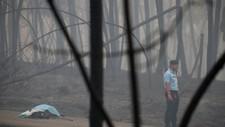 En politimann står ved en person som omkom i skogbrann i Portugal - Foto: Rafael Marchante/Reuters