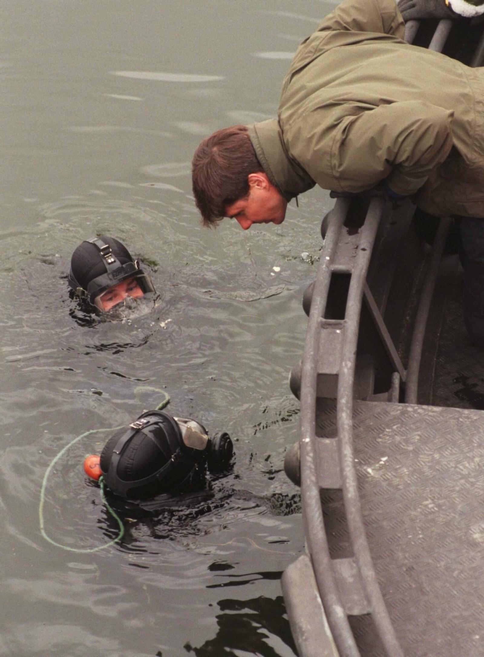 Politiets dykkere på veg opp fra vannet ved Tegelbacken i Stockholm etter å ha dykket etter våpenet som skal ha blitt brukt til å drepe Olof Palme. Det ble funnet en pistol på bunnen under søket.