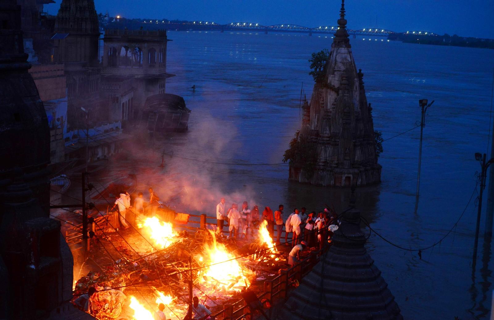 Indiske sørgende under en kremasjon på taket til en bygning i Varanasi i India den 23. august. Den hellige byen Varanasi har blitt tvunget til å stoppe kremasjoner langs elven Ganges på grunn av farlige flommer. Mer enn 100.000 mennesker har måttet flykte fra hjemmene sine de siste dagene etter at elver har gått over breddene.