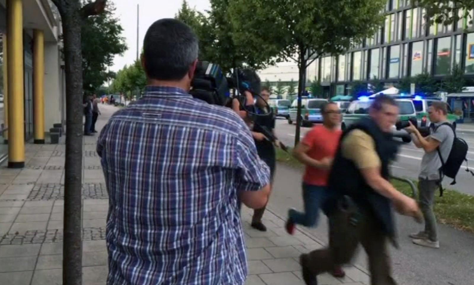 STOR USIKKERHET: Bevæpnet politi springer forbi media på gatene i München. Personen som avfyrte skudd inne på et kjøpesenter fredag kveld er ennå ikke pågrepet. Store mengder politi har rykket ut.