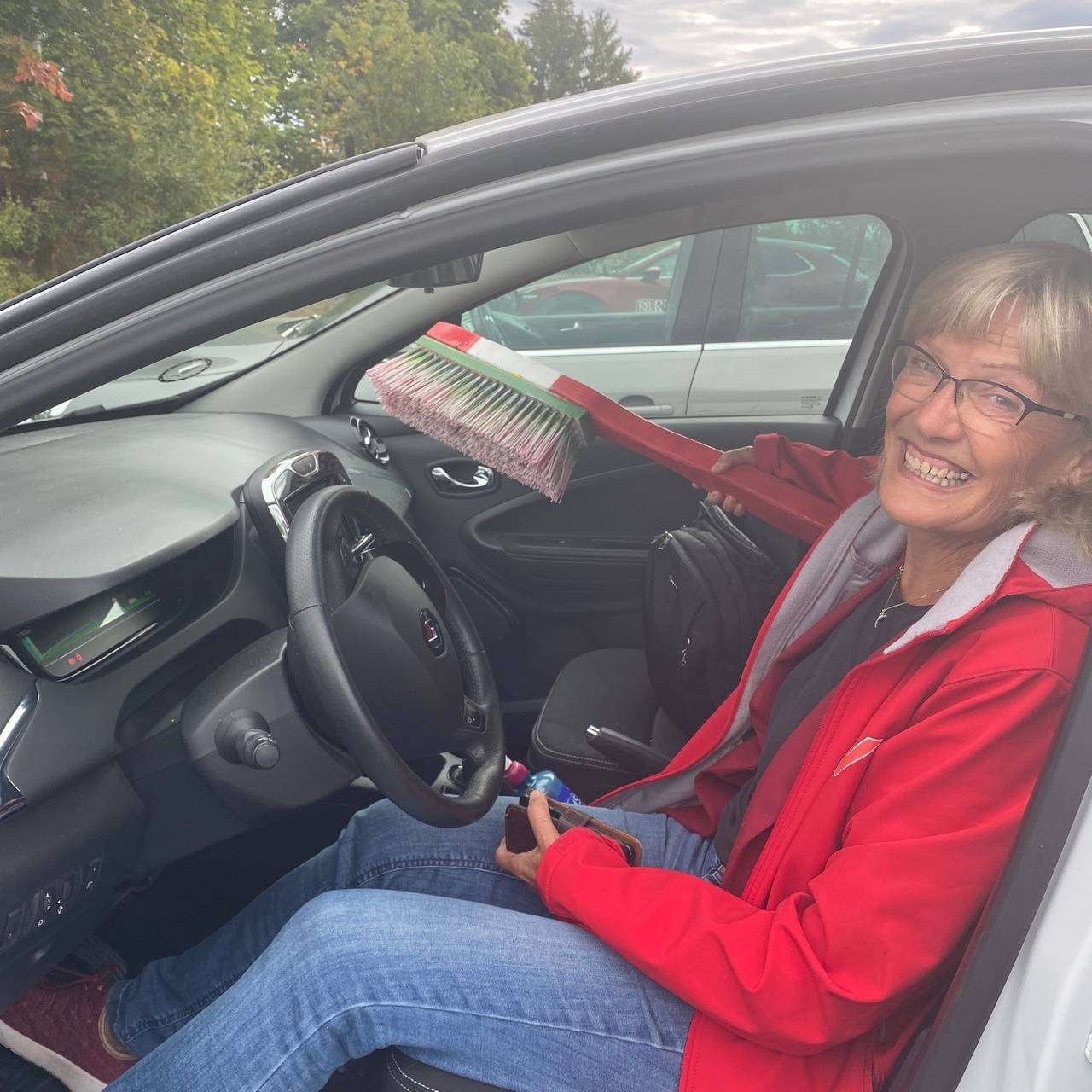 Karin Andersen i bil med diger tannbørste i passasjersetet