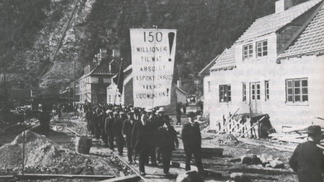 Alt i 1917 gjekk arbeidarane i demonstrasjonstog i Høyanger. Her handlar det om mat, dei kravde at det ikkje skulle eksporterast matvarer frå Noreg. Ukjend fotograf. Eigar: Hydro-arkivet.