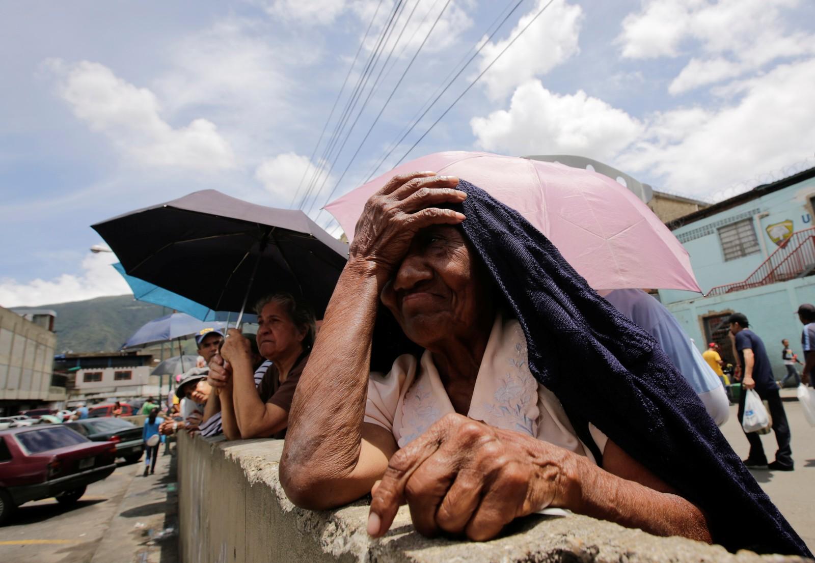 Køståing i Venezuela. Vanlige innbyggere i Caracas må stå i kø i flere timer utenfor matbutikken for å kjøpe matkuponger og basismatvarer.