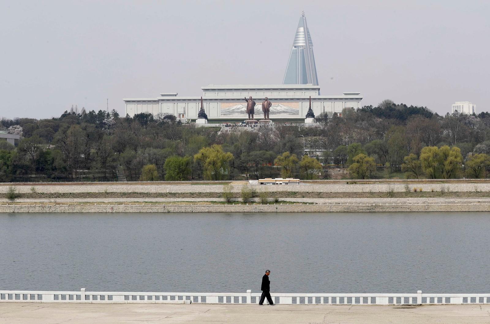 En mann spaserer langs elva Taedong med bronsestatuene av Kim Il-sung og Kim Jong-il i bakgrunnen.
