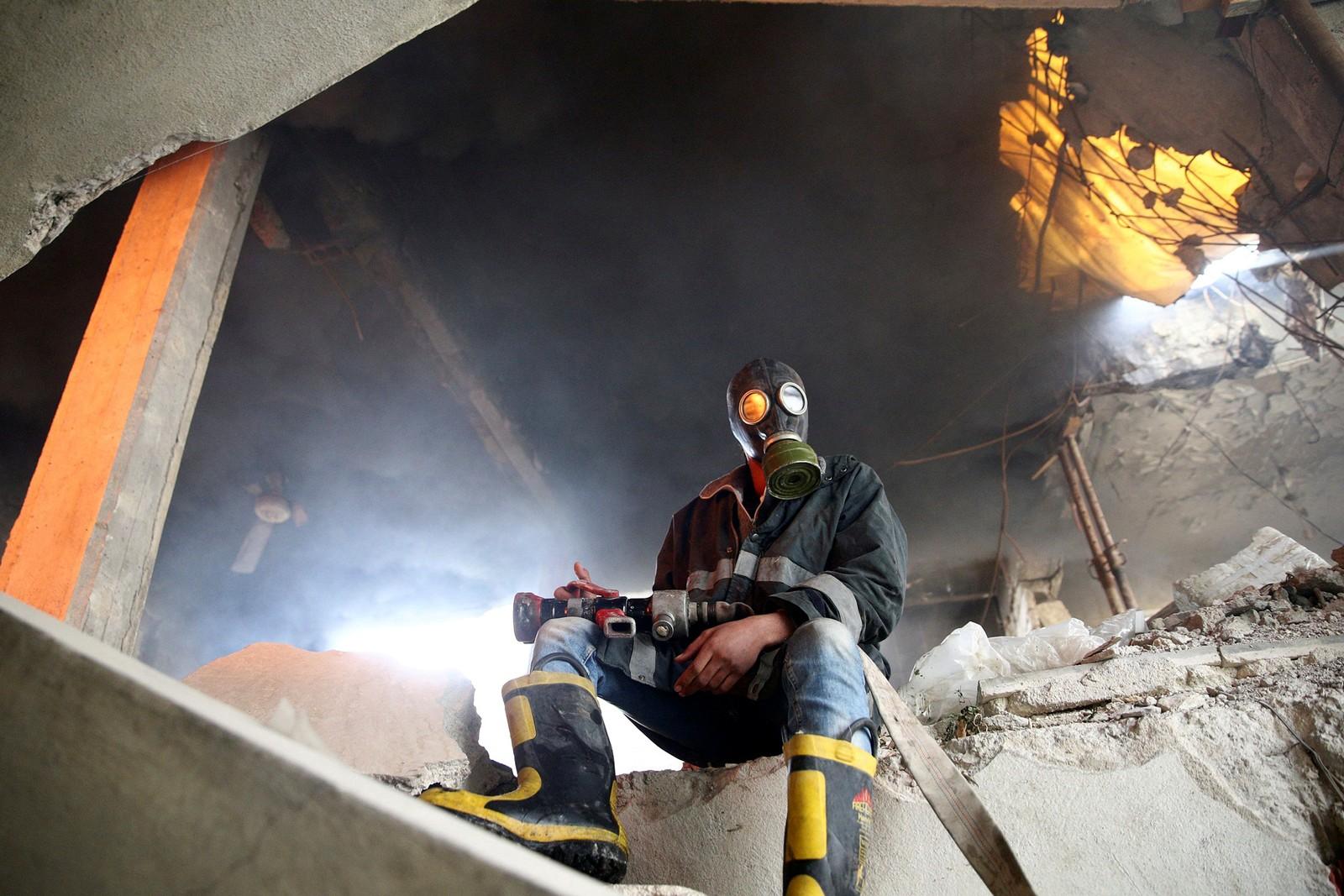 Et medlem av sivilforsvaret sitter i en bygning som har blitt bombet i Damaskus i Syria.