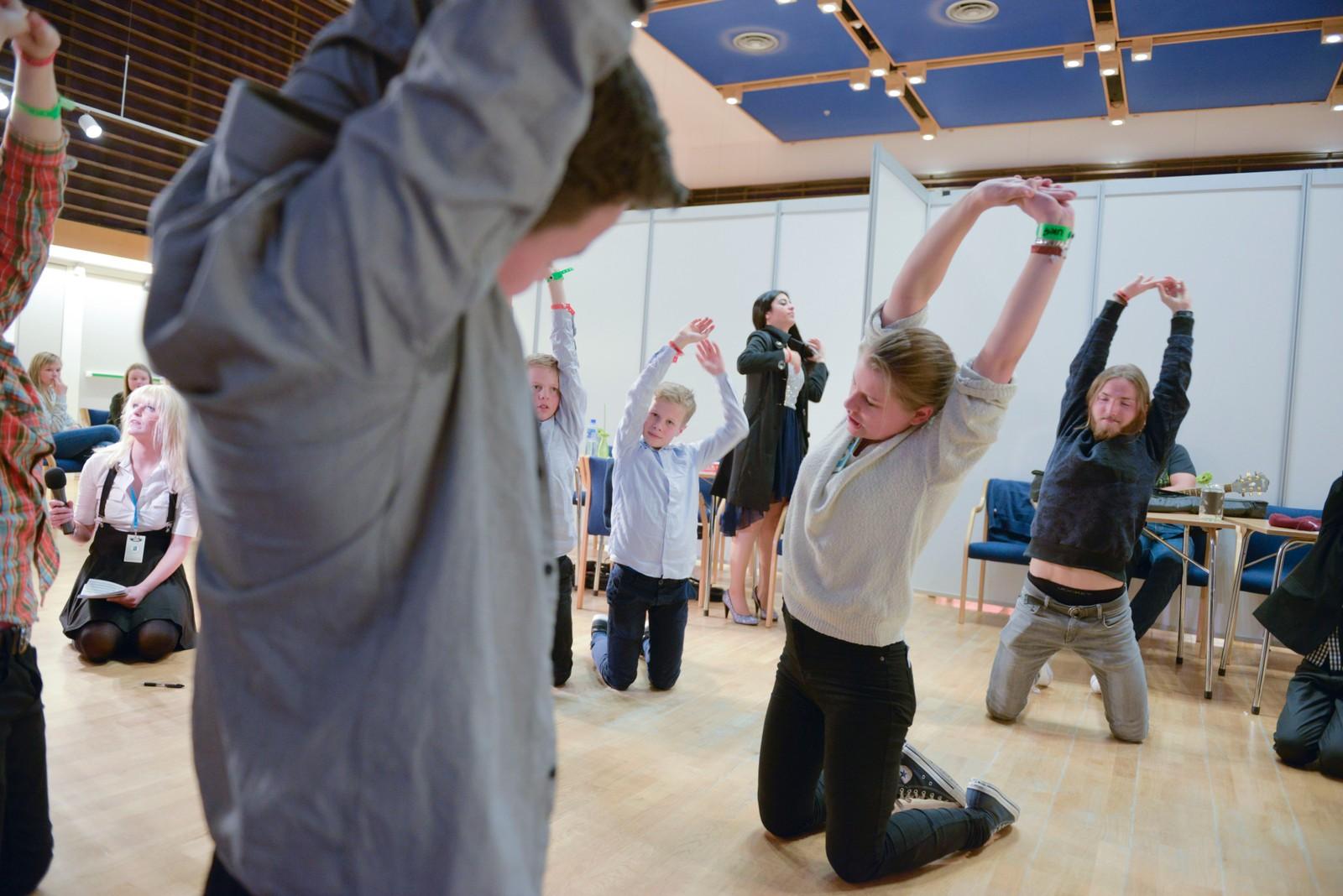 Trivselsleiar Marie Falkevik Tungevåg får med seg dei unge artistane på yogaøving før dei skal i elden.