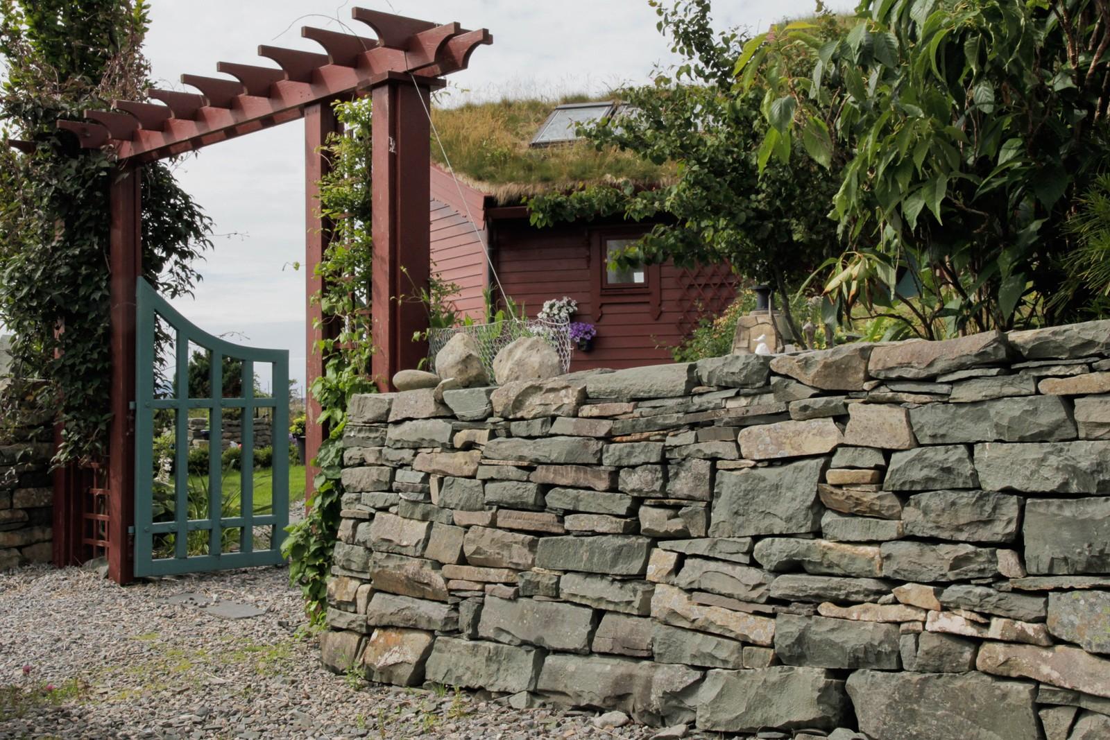Steinen Berit Steen har bygd mur av har dei samla rundt på øya Hovden, og den grønmåla porten har ho snikra sjøl.