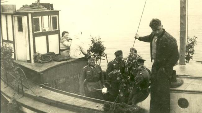 """Motorbåten """"Brenning"""" med tyske offiserar om bord. Det er truleg Hjalmar Brendsdal som står til høgre. Den 24. februar 1943 gjekk båten frå Korssund, i 1976 vart restar av båten funne på Gjøringebøvika i Førdefjorden. Brørne Arthur og Hjalmar Brendsdal har ingen sett meir til. Fotoet er utlånt av Eivind Fossheim"""