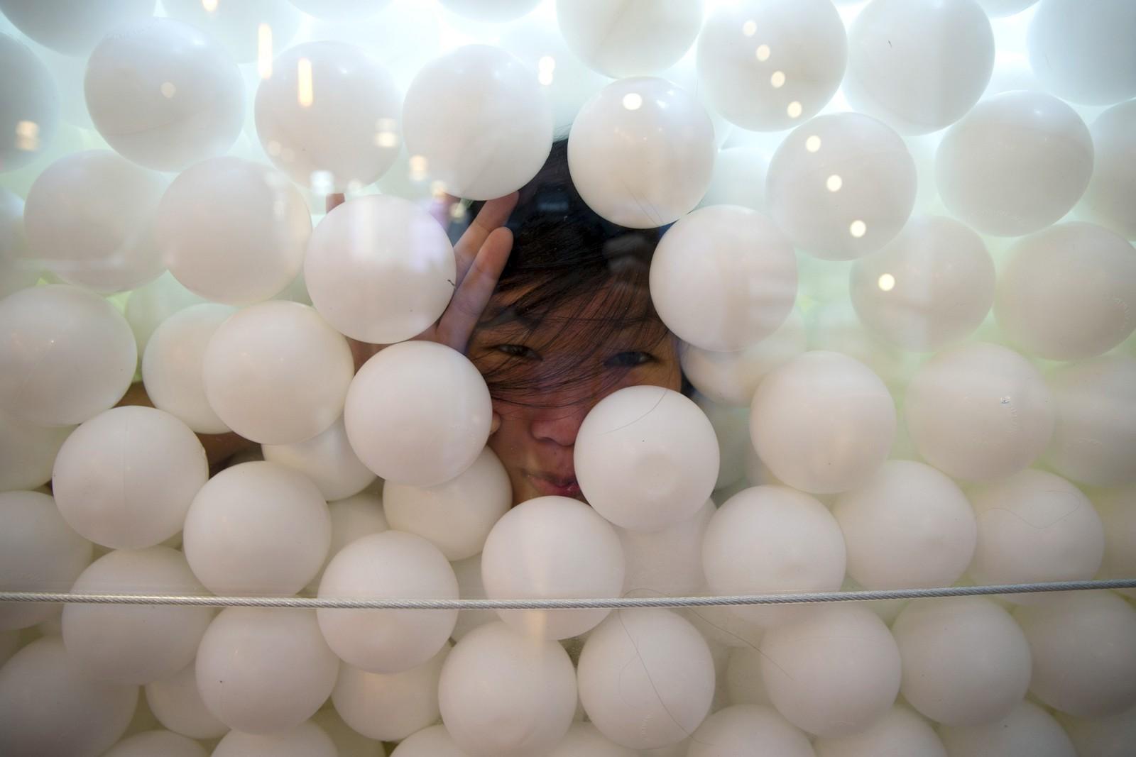 """En kvinne titter ut av installasjonen """"JumpIn!""""; en ballbinge bestående av 81.000 hvite baller. Kunstprosjektet, som visstnok skal frambringe kreativitet, er åpent for publikum i New York fram til 21. september."""