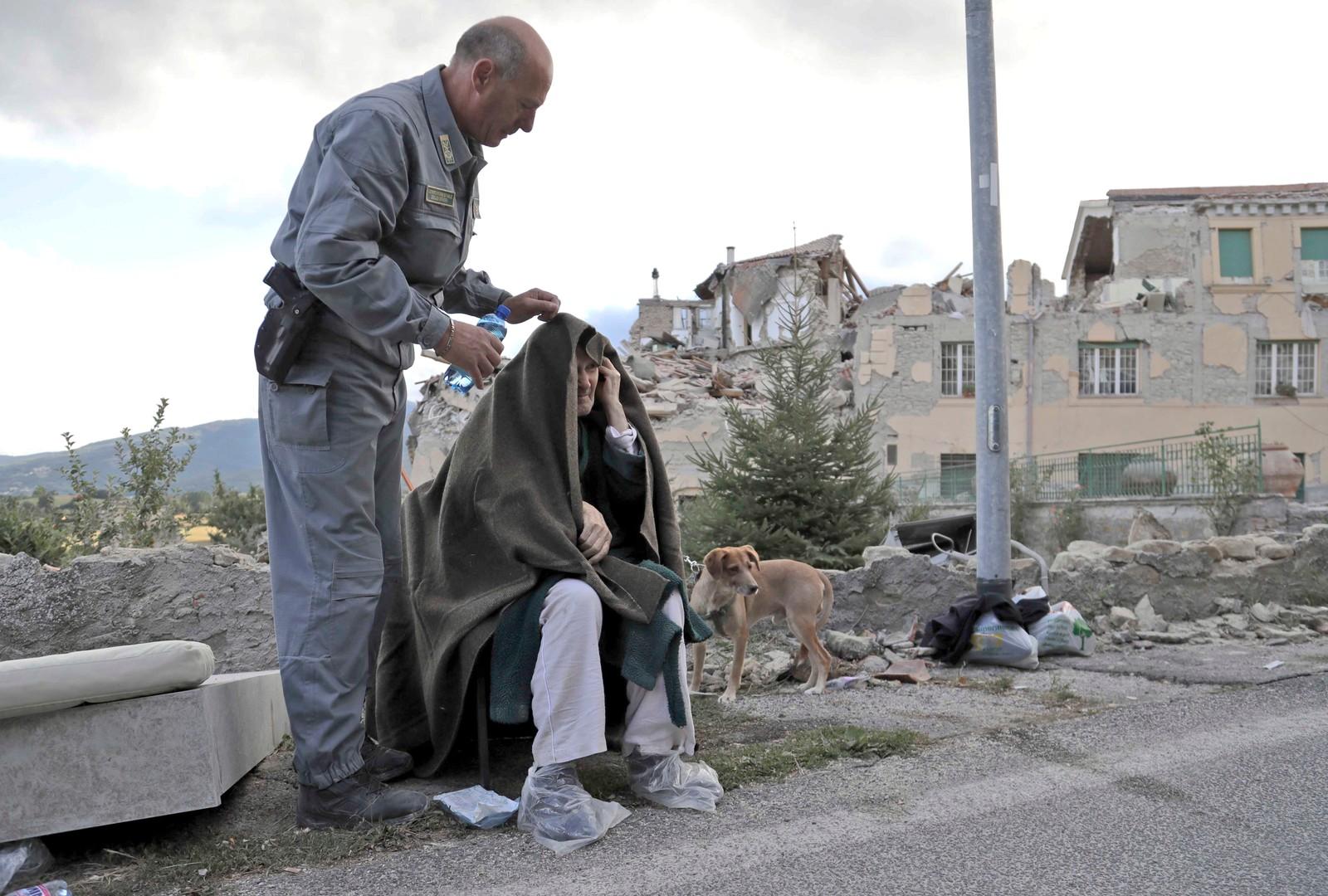 En gammel mann blir tatt hånd om av redningsmannskaper.