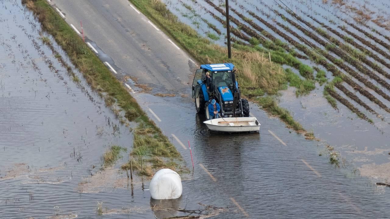 Vannet står høyt over veien. En traktor løfter en båt og en høyball i plast flyter i vannet.