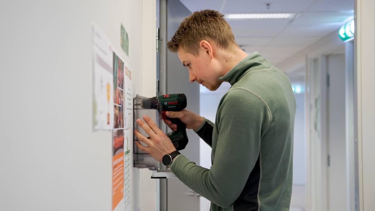 Pedagog Håkon Hvistendahl henger opp en Antibac-stasjon i lunsjrommet til de ansatte. Hånddesinfeksjon skal være tilgjengelig der det ikke er mulig å vaske hender.