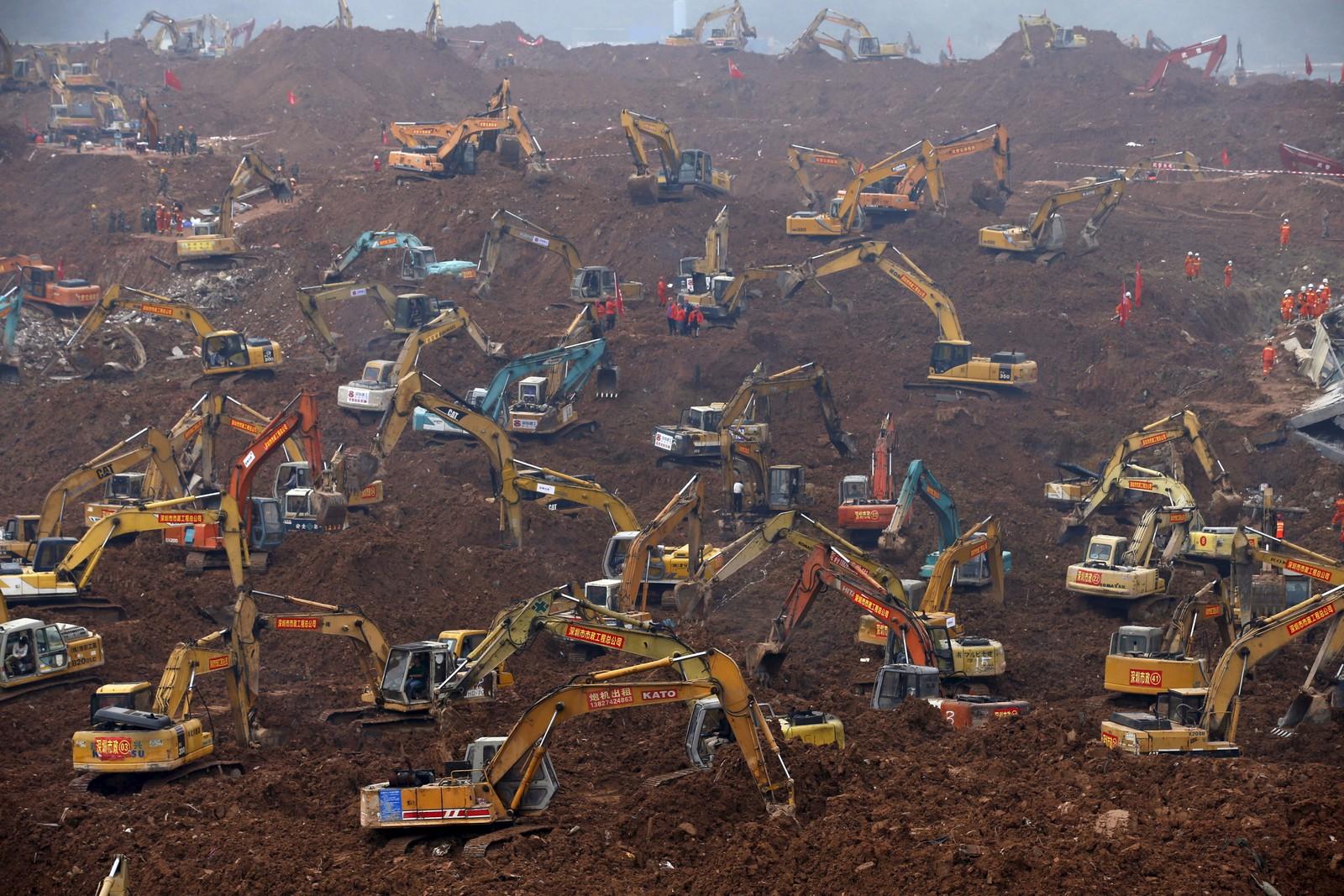 Gravemaskiner i gang med redningsarbeidet etter et jordskred i byen Shenzhen i Kina søndag. Skredet skyldes trolig at en enorm fylling med jord, skrot og bygningsavfall kollapsa. To er bekreftet døde og minst 73 savnet.